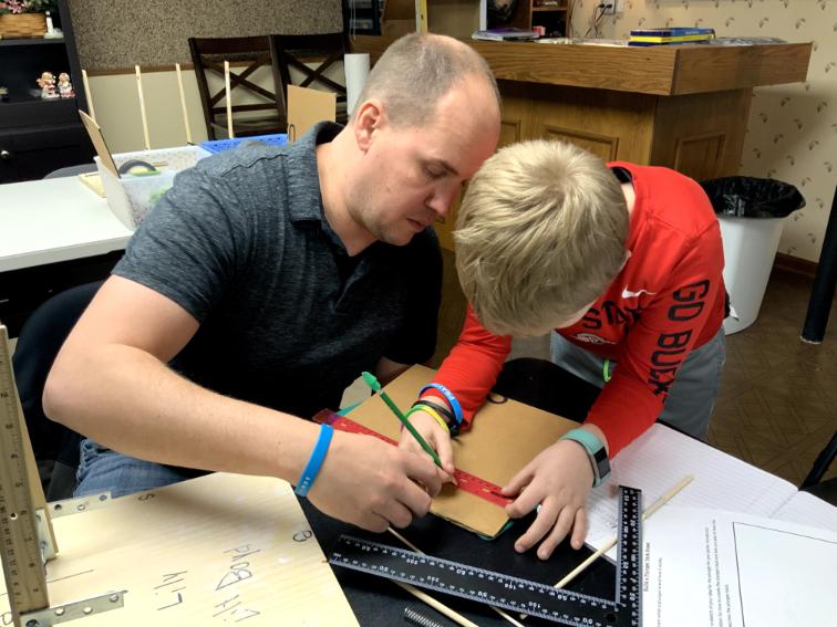 father and son measure a board